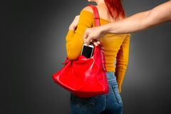 The thief steals from the bag. The robber coming up from the back to the girl secretly pulls her smartphone out of her bag stock photography