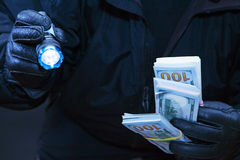 Thief steals money in darkness. Thief steals in darkness with a flashlight in his hand Stock Photo