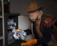 A thief steals money from the safe Stock Image
