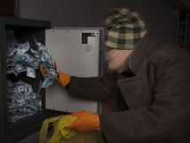 A thief steals money from the safe Royalty Free Stock Photo