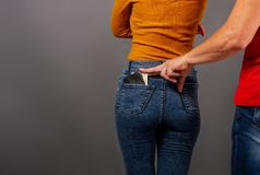 The thief steals the wallet. The thief, stepping up imperceptibly behind the girl, is trying to steal a purse with dollar bills from the back pocket of jeans stock photos