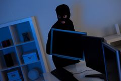 Thief steeling a computer Royalty Free Stock Photography