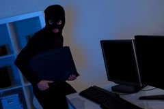 Thief steeling a computer Stock Photo