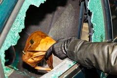 A thief stole a purse from car. A thief stole a purse from a car through a broken side window stock photos