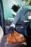 A thief stole a purse from car. A thief stole a purse from a car through a broken side window stock image