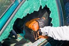 A thief stole a purse from car. A thief steals a purse from a car through a broken side window Stock Photos