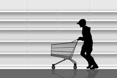 Thief in a supermarket. Silhouette of a man in a cap running with an empty shopping caddy in front of empty shelves of a supermarket Royalty Free Stock Photography