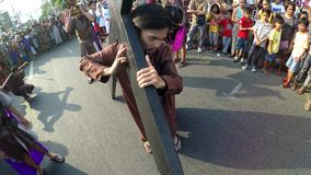 Thief takes the cross from Jesus Christ. crucifixion reenactment. San Pablo City, Laguna, Philippines - April 1, 2016: Unidentified people playing role of Thief stock footage