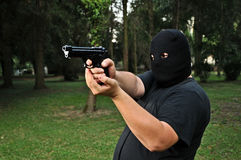 Thief threatening with a gun. Masked thief threatening with a gun Royalty Free Stock Images