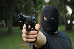 Thief threatening with a gun. Masked thief threatening with a gun Royalty Free Stock Photo