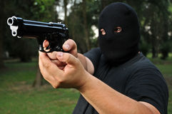 Thief threatening with a gun. Masked thief threatening with a gun Royalty Free Stock Photos