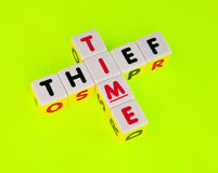 Thief of time. Text ' thief ' and ' time ' inscribed in uppercase letters on small white cubes and arranged crossword style with common letter  ' i ' , concept Royalty Free Stock Photography