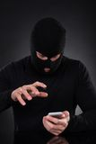 Thief trying to access a stolen mobile phone royalty free stock photos