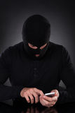 Thief trying to access a stolen mobile phone stock photos