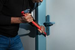 Thief Trying To Break The Door With Crowbar stock images