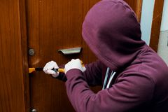 Hooded burglar forcing an home door lock. Thief trying to break house entrance door lock royalty free stock photos