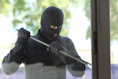 Thief trying to open a house window stock image
