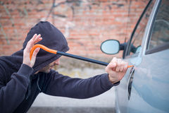 Thief trying to pick the lock of parked car Stock Photos