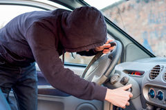 Thief trying to pick the lock of parked car Royalty Free Stock Photography