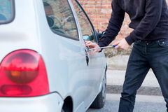 Thief trying to pick the lock of parked car Stock Photo