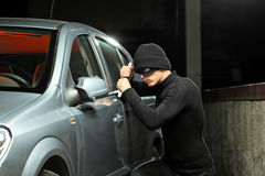 Thief trying to steal an automobile. A thief with a robbery mask trying to steal an automobile royalty free stock images