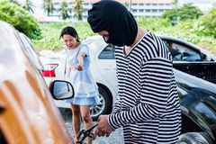Thief and crime. Thief is trying to steal the car at the public parking Stock Photos