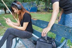 Thief trying to steal and walk away the wallet in the bag while. Women using mobile phone and listening to music on sofa in the park Royalty Free Stock Photography