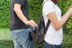 Thief trying to steal the wallet in the backpack in the park.  stock photo