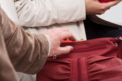 Thief trying to steal a wallet. Thief trying to take out the wallet from lady's purse Stock Photos