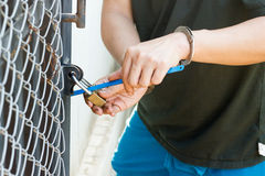 The thief uses a saw to cut the keys. Royalty Free Stock Image