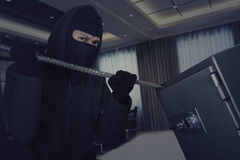 Thief using crowbar to open bank vault. Male thief wearing a mask and trying to open a safe-deposit box in the office Stock Photo