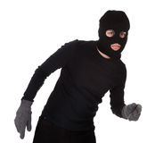 Thief wearing a balaclava. Dressed in blacked moving stealthily. Isolated on white Stock Images