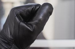 The thief, wearing black gloves, knocks on the window of the house to check if the owners are at home Royalty Free Stock Photography