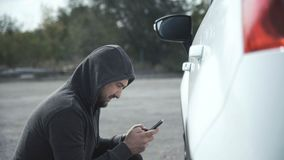 Thief breaking in car using mobile phone stock photos