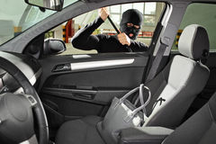 Thief wearing a mask trying to steal a bag. A thief wearing a robbery mask trying to steal a purse bag in a automobile stock photo