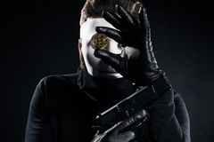 Thief in white mask holding gun royalty free stock images