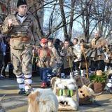 Thildren com os trajes tradicionais do kukeri marcha nas ruas de Pernik Imagem de Stock