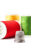 Thimble. Closeup view of thimble and colorful spools over white background Royalty Free Stock Images