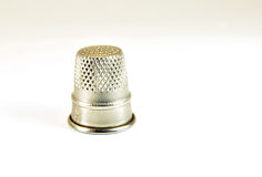 Thimble. Closeup of an old metal thimble on white background Stock Image