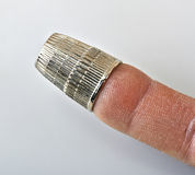 Old thimble on finger Royalty Free Stock Image