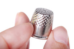 Thimble in hand Stock Images