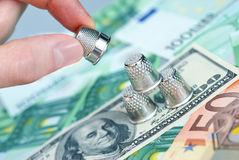 Thimble in hand and money. Dollars and euros Stock Images