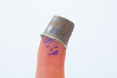 Thimble on middle finger, closeup Royalty Free Stock Photo
