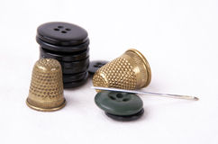 Thimble with a needle and black buttons. On white background Royalty Free Stock Photo