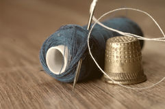 Thimble. And needles for sewing close-up on a background thread spools. macro Royalty Free Stock Photography