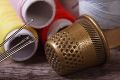 Thimble and needles for sewing closeup on a background thread� Royalty Free Stock Photos