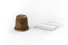 Thimble and needles on white background Royalty Free Stock Photos