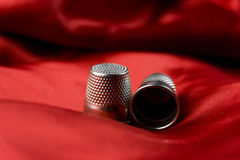 Thimble red. A detail of two thimbles on red satin background Stock Image