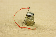 Thimble and a sewing needle with a thread on linen fabric, close up, warm natural tone Stock Photo