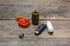 Thimble and spools of thread on an aged wooden surface Stock Images